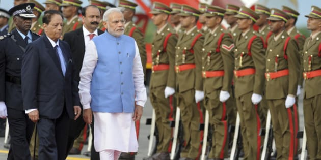 India's Prime Minister Narendra Modi, center-left, inspects an honour guard accompanied by Prime Minister of Mauritius Anerood Jugnauth, left, upon his arrival at the airport on Mauritius Island, in the Republic of Mauritius Wednesday, March 11, 2015. According to the Indian Prime Minister's website Modi is leading a delegation on a three nation tour of Seychelles, Mauritius and Sri Lanka to strengthen ties between the countries. (AP Photo/George Michel)