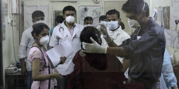 Indian medical staff attending to a patient are seen through the glass of an isolation ward for swine flu at the Civil Hospital in Ahmadabad, India, Wednesday, Feb. 25, 2015.The west Indian city has banned large public gatherings in an attempt to halt the spread of swine flu, which has claimed more than 900 lives nationwide in 11 weeks. (AP Photo/Ajit Solanki)