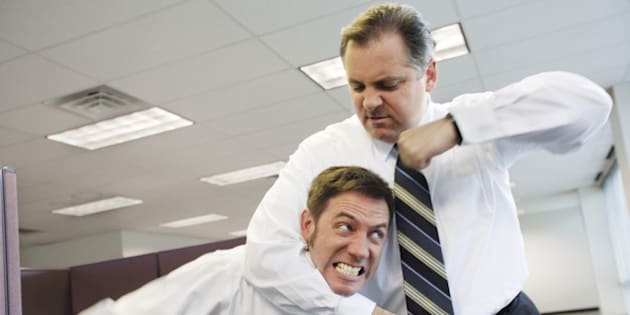 Two businessmen fighting in office, one in headlock