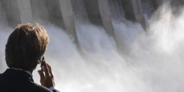 Businessman talks on mobile phone, dam spillway