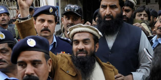 Zaki-ur-Rahman Lakhvi, the main suspect of the Mumbai terror attacks in 2008, raises his fist after his court appearance in Islamabad, Pakistan, Thursday, Jan. 1, 2015. Lakhvi was sent to judicial remand in an abduction case by a court, official said. (AP Photo/B.K. Bangash)