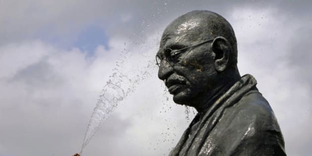 """A worker sprays water on a statue of the late Mahatma Gandhi on the eve of his birth anniversary at Gandhi Park in Bhubaneswar, eastern India, Monday, Oct. 1, 2012. Gandhi, known as the """"Father of the Nation,"""" was instrumental in the movement that lead to India's independence from Britain in 1947. (AP Photo/Biswaranjan Rout)"""