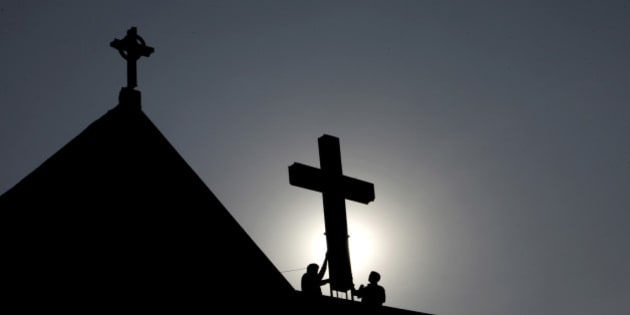 Indian workers paint a cross atop a church ahead of Christmas in Hyderabad, India, Monday, Dec. 19, 2011. Christians make up about 2 percent of India's 1 billion-plus population. (AP Photo/Mahesh Kumar A.)