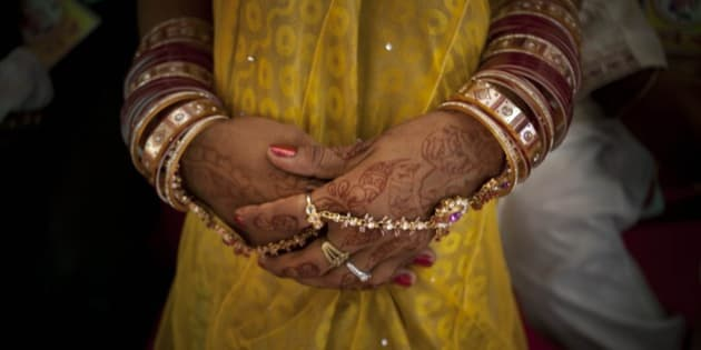 An Indian bride who has her hand decorated waits for a ceremony to begin during a mass wedding organized by a social organization for a hundred couple from the economically weaker sections of the society in New Delhi, India, Sunday, June 15, 2014. Mass weddings are organized by social organizations primarily to help families who cannot afford the high ceremony costs as well as the elaborate dowry that is customary in many communities. (AP Photo/Tsering Topgyal)