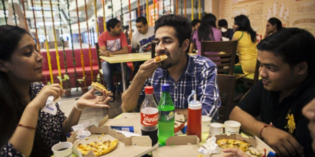 Customers eat at a Domino's Pizza outlet, operated by Jubilant Foodworks Ltd., after the opening of the company's 600th Indian restaurant in New Delhi, India, on Monday, Aug. 26, 2013. Dominos is the worlds second-largest pizza chain. Photographer: Prashanth Vishwanathan/Bloomberg via Getty Images