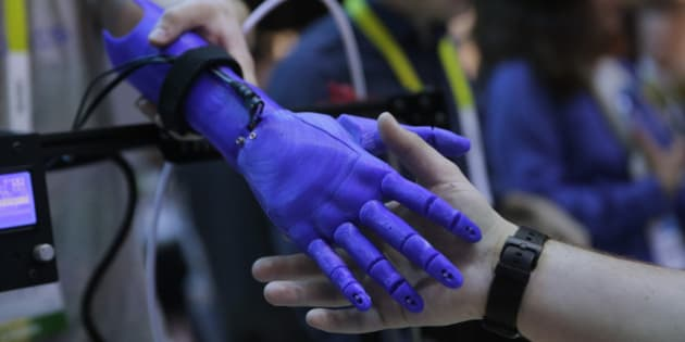 An attendee shakes hands with a 3D-printed robotic prosthetic arm created based on an image scanned with Intel's RealSense 3D camera, at the International CES Wednesday, Jan. 7, 2015, in Las Vegas. (AP Photo/Jae C. Hong)