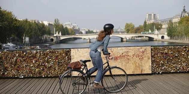 A woman rides a bicycle on the Pont des Arts with its railings covered by lovelocks on September 23, 2014  in Paris. Paris officials have put up long panels on the city's iconic Pont des Arts in the latest attempt to stop lovers sealing their passion with padlocks attached to the bridge. Just over the busy summer period, romantic tourists to the world's most visited city attached more than 700,000 love lock on several Paris bridges, said City Hall authorities. 'On the Pont des Arts alone, 15 grills have had to be removed for safety reasons. Each of these panels were carrying nearly 500 kilogrammes, more than four times the maximum weight,' city hall said.   AFP PHOTO / THOMAS SAMSON        (Photo credit should read THOMAS SAMSON/AFP/Getty Images)