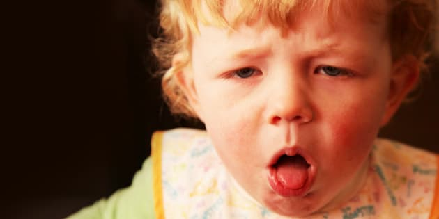 A young boy (18 months) with a nasty cough, coughing with his mouth open and tongue poking out