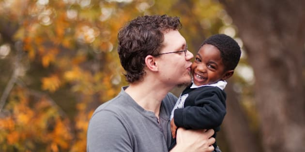 Father kissing his adopted toddler son who is African-American at Old Settler's Park in Round Rock, Texas.