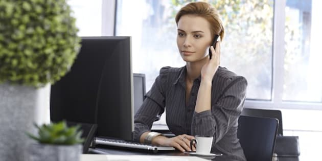 Attractive businesswoman working in green office, talking on mobilephone, using computer..