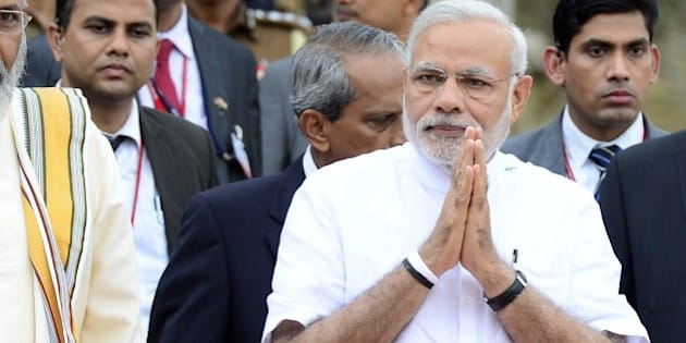 Indian Prime Minister Narendra Modi (R) and the Sri Lankan chief minister of the northern province C. V. Vigneswaran (L) arrive for a ceremony to hand over Indian-funded houses to Tamils displaced or made destitute by fighting in Jaffna, some 400 kilometres (250 miles) north of Colombo on March 14, 2015.  Narendra Modi landed in Jaffna on March 14, becoming the first Indian prime minister to visit Sri Lanka's war-ravaged northern Tamil heartland.  AFP PHOTO / Lakruwan WANNIARACHCHI        (Photo credit should read LAKRUWAN WANNIARACHCHI/AFP/Getty Images)