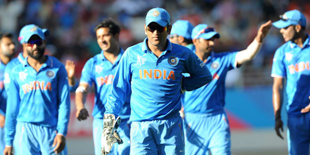India captain MS Dhoni leads his team from the field after they dismissed Zimbabwe for 287 runs during their Cricket World Cup Pool B match in Auckland, New Zealand, Saturday, March 14, 2015. (AP Photo/Ross Setford)