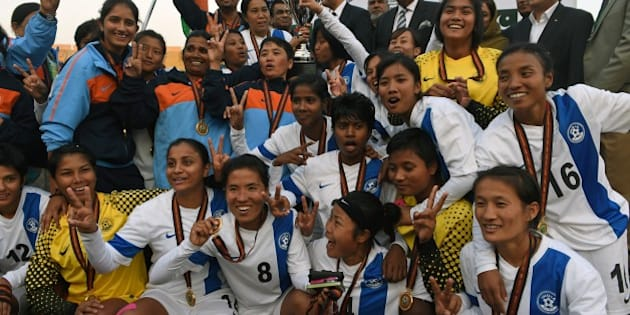 Indian women football team members celebrate their victory after defeating Nepal in the final of the 3rd South Asian Football Federation (SAFF) women's football championship at the Jinnah Stadium in Islamabad on November 21, 2014. India defeated Nepal 5-0.  AFP PHOTO/Farooq NAEEM        (Photo credit should read FAROOQ NAEEM/AFP/Getty Images)