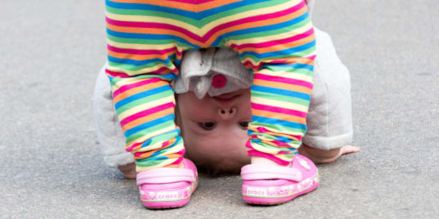 TORONTO, ONTARIO, CANADA - 2014/09/20: Cute child looking through her legs with the head close to the floor. (Photo by Roberto Machado Noa/LightRocket via Getty Images)