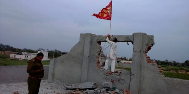 HISAR, INDIA - MARCH 16: A red flag hoisted on an under construction church that was vandalized by some miscreants at village Kaimri on March 16, 2015 in Hisar, India.  The under-construction site was vandalized by some miscreants and idol of a Hindu god was placed inside its premises on March 13. Police has booked 14 people for rioting, damaging place of worship, theft and promoting enmity on complaint by the church priest. Tension prevails in the area with the villagers demanding that cases be withdrawn against those among the booked with no hand in the incident. (Photo by Manoj Dhaka/Hindustan Times via Getty Images)