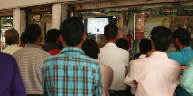 CHANDIGARH, INDIA - MARCH 25:  Local men gather around a shop window to watch the television coverage of the Indian Premier League cricket in sector 22 market place on March 25, 2010 in Chandigarh, India.  (Photo by Mark Kolbe/Getty Images)