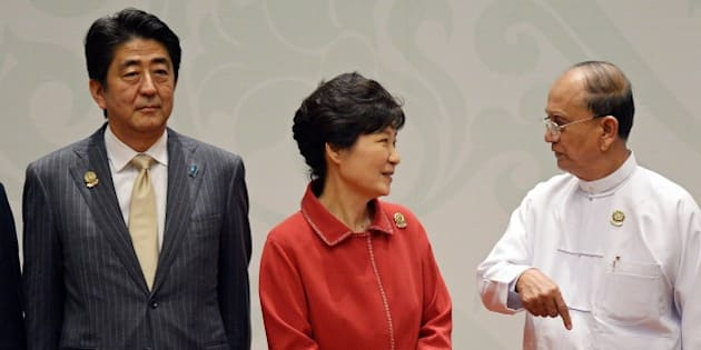(L-R) Japanese Prime Minister Shinzo Abe looks on as South Korean President Park Geun-Hye speaks with Myanmar's President Thein Sein ahead of a 'family picture' during the 17th ASEAN Plus THree Summit at the Myanmar International Convention Center in Myanmar's capital Naypyidaw on November 13, 2014.  The Association of Southeast Asian Nations (ASEAN) and East Asia summits, held in the purpose-built capital of Naypyidaw this week, are the culmination of a year of diplomatic limelight for Myanmar after long decades shunted to the sidelines under its former military rulers. AFP PHOTO / Christophe ARCHAMBAULT        (Photo credit should read CHRISTOPHE ARCHAMBAULT/AFP/Getty Images)
