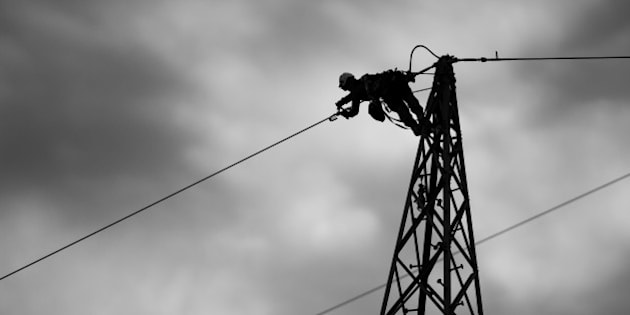 PFUNGSTADT, GERMANY - FEBRUARY 26:  (EDITOR'S NOTE: This image has been converted to black and white.) Workers install an electricity transmission tower, also called an electricity pylon, with a new high-voltage cable on February 26, 2015 in Pfungstadt, Germany.  (Photo by Thomas Lohnes/Getty Images)
