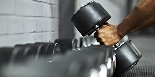 Strong black male picking up dumbbells from selection of free weights in gym, ready for workout