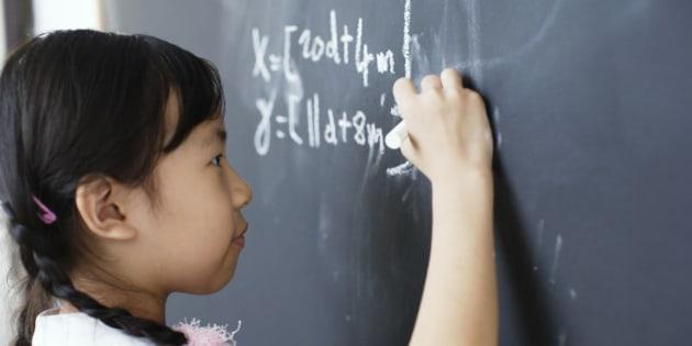 Girl writing on blackboard in classroom