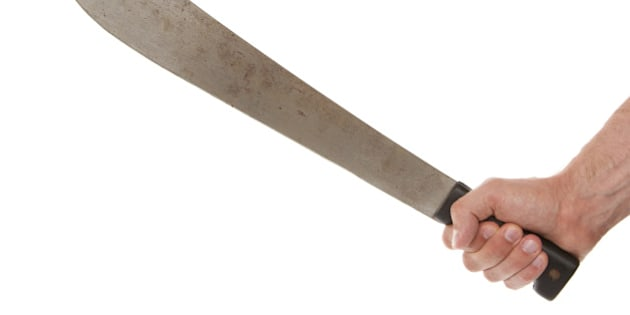 Man holding a machete, isolated on white