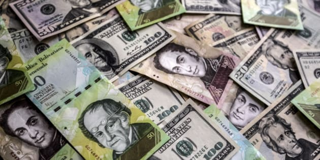 Venezuelan bolivar notes and various denominations of U.S dollar bills are arranged for a photograph in Caracas, Venezuela, on Sunday, Feb. 22, 2015. A decline in oil revenue has exacerbated the drop in the bolivar, which has lost 90 percent of its value against the U.S. dollar on the black market since President Nicolas Maduro came to office two years ago. Photographer: Meridith Kohut/Bloomberg via Getty Images