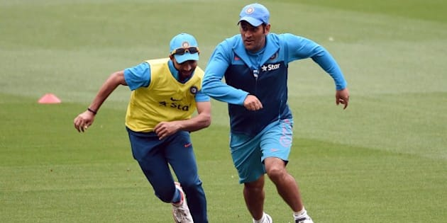 Indian cricket captain Mahendra Singh Dhoni (R) dribbles the ball past teammate Ajinkya Rahane (L) in a game of football during a training session ahead of their 2015 Cricket World Cup quarter-final match against Bangladesh, in Melbourne on March 17, 2015.    AFP PHOTO / William WEST   --IMAGE RESTRICTED TO EDITORIAL USE - STRICTLY NO COMMERCIAL USE--        (Photo credit should read WILLIAM WEST/AFP/Getty Images)