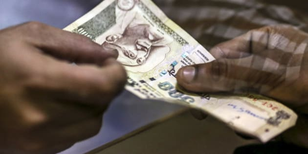 A customer deposits a Indian five-hundred rupee banknotes at a branch of the HDFC Bank Ltd. in Mumbai, India on Thursday, Aug. 22, 2013. India's rupee slumped to an all-time low after Federal Reserve minutes showed the U.S. is getting closer to reducing stimulus that has fueled demand for emerging-market assets. Photographer: Dhiraj Singh/Bloomberg via Getty Images