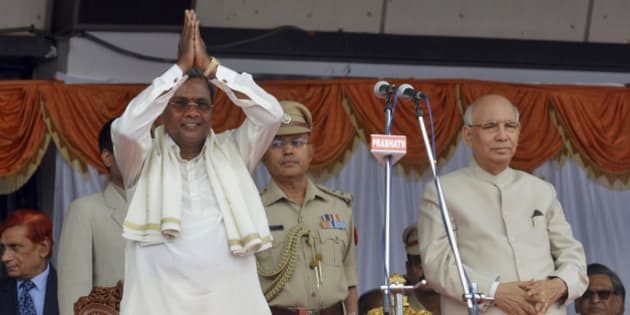 India's ruling Congress party leader and new Chief Minister of Karnataka state K. Siddaramaiah, left, greets his supporters after administering the oath of office in the presence of Governor H.R. Bhardwaj, right, at the Kanteerva Stadium in Bangalore, India, Monday, May 13, 2013. Siddaramaiah, 64, administered the oath of office Monday in front of thousands of supporters marking the return of the administration back to the hands of Congress, in the state, after more than 7 years, according to local reports. (AP Photo/Kashif Masood)