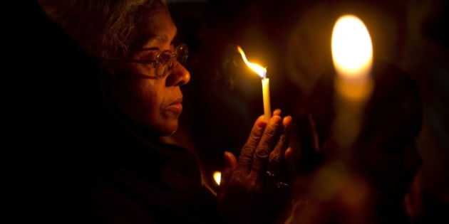 A Christian woman prays as they hold a candle light vigil to condemn the gang rape of a nun at a Christian missionary school in eastern India outside the Sacred Heart cathedral in New Delhi, India, Monday, March 16, 2015.  According to police a nun in her 70s was gang-raped by a group of bandits when she tried to prevent them from committing a robbery in the Convent of Jesus and Mary School in West Bengal state's Nadia district. The attack early Saturday is the latest crime to focus attention on the scourge of sexual violence in India. (AP Photo/Saurabh Das)