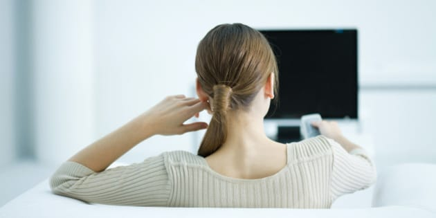 Young woman sitting in armchair watching TV, holding remote, rear view
