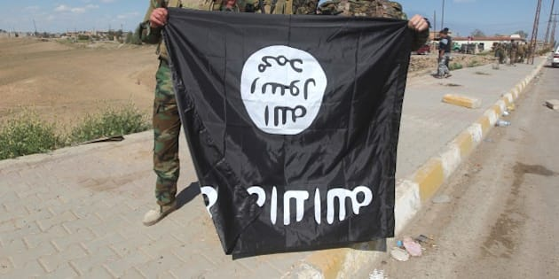 Iraqi Sunni and Shiite fighters pose for a photo with an Islamic State (IS) group flag in the Al-Alam town, northeast of the Iraqi city of Tikrit, on March 17, 2015 after recapturing the town from IS fighters earlier in the month. Loyalists had already failed three times to retake the nearby city of Tikrit, the hometown of Saddam Hussein, which was captured by IS last summer. AFP PHOTO / AHMAD AL-RUBAYE        (Photo credit should read AHMAD AL-RUBAYE/AFP/Getty Images)
