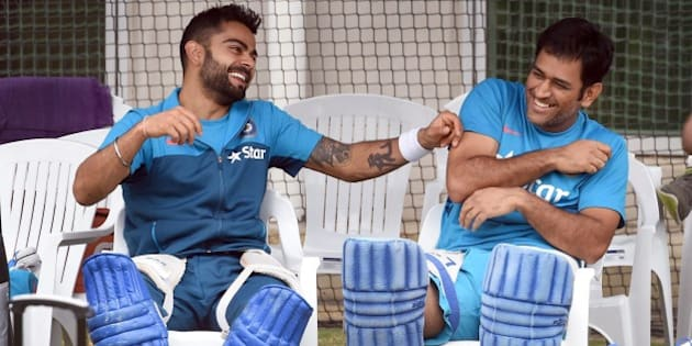Indian cricket players Virat Kohli (L) and captain Mahendra Singh Dhoni (R) share a lighter moment during a training session ahead of their 2015 Cricket World Cup quarter-final match against Bangladesh in Melbourne on March 18, 2015.    AFP PHOTO / William WEST   