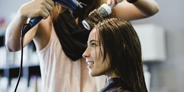 Stylist blow drying client's hair in salon