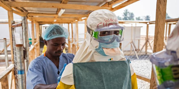 In this photo taken on Monday, March 2,  2015, a health care worker prepares a colleague's virus protective gear before entering a high risk zone at an Ebola virus clinic operated by the International Medical Corps in Makeni, Sierra Leone.  According to the head of the national Ebola response Centre, complacent behavior in Sierra Leone has led to a worrying spike in confirmed Ebola cases over the past week in four districts, Alfred Palo Conteh said Thursday, March 12, 2015.  (AP Photo/ Michael Duff)