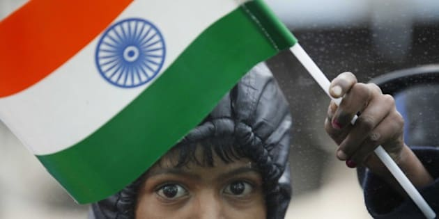 NEW DELHI, INDIA - JANUARY 26: A street child selling Indian flag  at India Gate after the ceremony of 66th Republic Day of India, on January 26, 2015 in New Delhi, India. President of United States of America (USA) Barack Obama is the chief guest for this Republic Day. Rain failed to dampen spirits at India's Republic Day parade January 26 as US President Barack Obama became the first US president to attend the spectacular military and cultural display in a mark of the nations' growing closeness. Colourful images of India's cultural heritage, manoeuvres by fighter aircraft, military prowess and march past by armed forces were on majestic display. The main attractions of the parade were scintillating show of air power, fascinating tableaus depicting the diverse culture and dance performances by colourfully dressed schoolchildren. Around 25,000 security personnel were deployed across the city while the commandos of the Indo-Tibetan Border Police and Delhi Police kept vigil at important locations. (Photo by Raj K Raj/Hindustan Times via Getty Images)