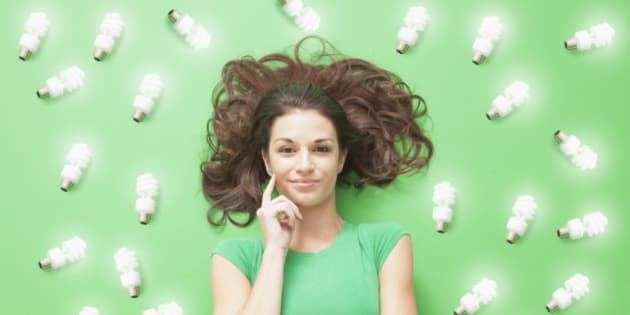 Girl laying on Green background with CF light bulbs around her