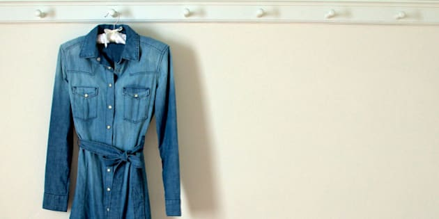 Weathered denim dress with pearl buttons hanging against plain white wall.