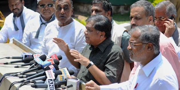 Indian leaders and members of the opposition in the Karnataka State Legislative Assembly, gather outside the Raj Bhavan after submitting a memorandum to the State Governor urging him to pressurise the Congress-ruled state government to hand over the inquiry into the controversial death of a popular Indian Administrative Service (IAS) Officer, D.K. Ravi to the Central Bureau of Investigation (CBI), in Bangalore on March 19, 2015.  Additional commissioner of commercial taxes (Enforcement), Ravi (35) was found hanging from a ceiling fan of his flat in Bangalore on March 16, with police suspecting it to be prima facie a case of suicide.  AFP PHOTO / Manjunath KIRAN        (Photo credit should read Manjunath Kiran/AFP/Getty Images)