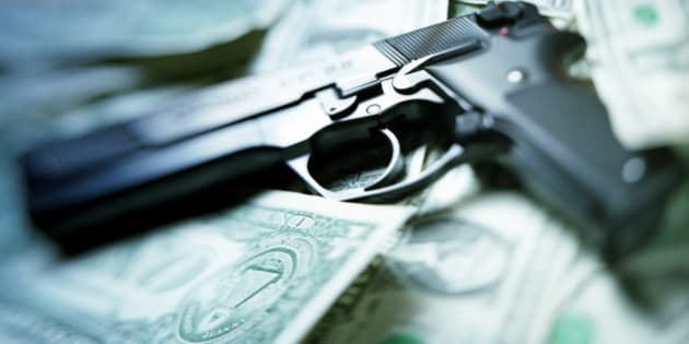 pistol lying on dollar notes