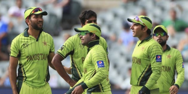 Pakistan's Umar Akmal, center, celebrates with teammates after taking a catch to dismiss Ireland's Stuart Thompson during their Cricket World Cup Pool B match in Adelaide, Australia, Sunday, March 15, 2015. (AP Photo/James Elsby)