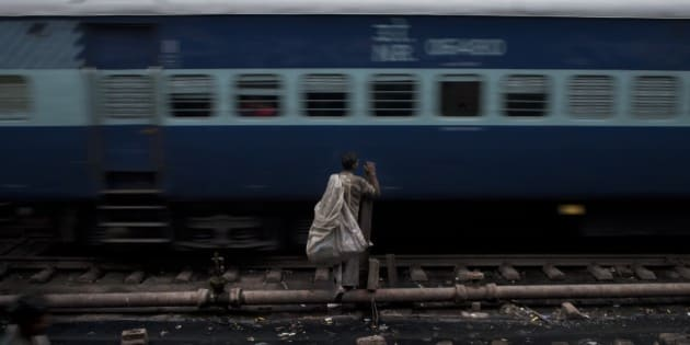 An Indian ragpicker waits for a train to pass by as he tries to cross railway tracks in New Delhi, India, Wednesday, Feb. 25, 2015. India on Thursday is expected to table the 2015 budget for the national railways system, which is one of the world's largest and serves more than 23 million passengers a day. (AP Photo/Bernat Armangue)