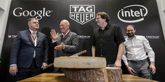 (L TO R) Swiss watchmaker Tag Heuer Director General Guy Semon, Tag Heuer CEO Jean-Claude Biver, Intel's new device general manager Michael Bell and Google's engineering director for Android wear David Singleton pose with a Swiss cheese during the anoucement on March 19, 2015 in Basel of a partnership between the watch brand, owned by the French luxury group LVMH and the two giants of the Silicon Valley. Luxury Swiss watchmaker Tag Heuer announced  it was joining forces with technology behemoths Google and Intel to develop a connected timepiece that can compete with the new Apple Watch.AFP PHOTO / FABRICE COFFRINI        (Photo credit should read FABRICE COFFRINI/AFP/Getty Images)