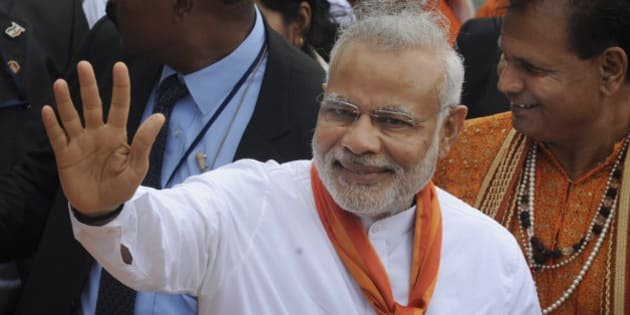 India's Prime Minister Narendra Modi waves during a visit to the crater lake of Grand Bassin (also known as Ganga Talao) during the second day of his visit to the Republic of Mauritius Thursday, March 12, 2015. According to the Indian Prime Minister's website Modi is leading a delegation on a three nation tour of Seychelles, Mauritius and Sri Lanka to strengthen ties between the countries. (AP Photo/George Michel)
