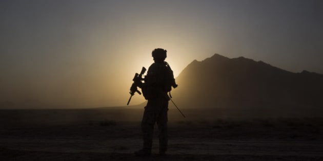 A soldier with the Canadian Army's 1st Battalion 22nd Royal Regiment prepares for an operation at sunrise Monday, June 27, 2011 in the Panjwaii district of Kandahar province, Afghanistan. Canadian combat operations will end in July as troops withdraw from the southern region and hand control over to the Americans. Canada will transition to a non-combat training role with up to 950 soldiers and support staff to train Afghan soldiers and cops in areas of the north, west and Kabul. (AP Photo/David Goldman)