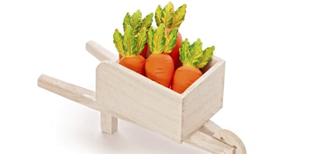Delicious orange toy carrot in a wooden cart isolated on white