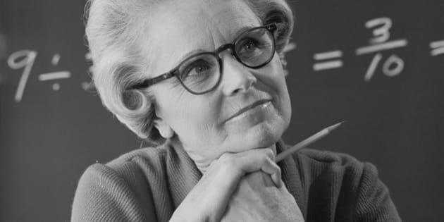 Senior female teacher with formulas in background, close-up