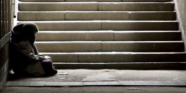 photo of beggar woman reading the book in undergrund subway