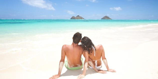 couple on beach vacation enjoying  sun on honeymoon. Lanikai beach and the Mokulua islands in kailua, oahu, hawaii