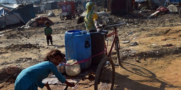 This photo taken on March 19, 2015 shows a girl helping her mother carrying water containers on a tricyle rickshaw to their shanty in Ghaziabad, east of  New Delhi. A new UN report launched in New Delhi on March 20 ahead of World Water Day on March 22 warned of an urgent need to manage the world's water more sustainably and highlight the problem of groundwater over-extraction, particularly in India and China. The report says global demand for water is increasing exponentially, driven largely by population growth. AFP PHOTO/ PRAKASH SINGH        (Photo credit should read PRAKASH SINGH/AFP/Getty Images)